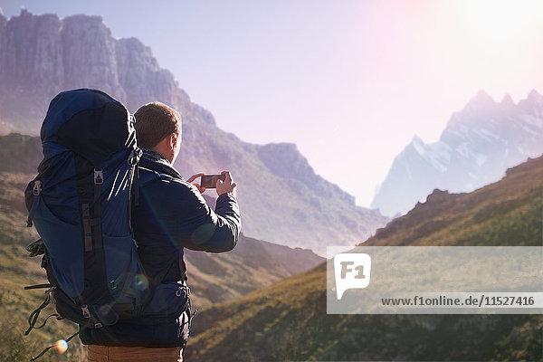 Junger Mann mit Rucksack mit Fotohandy im sonnigen Tal unter den Bergen
