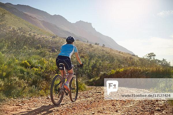 Junge Frau beim Mountainbiken auf sonniger  abgelegener Schotterpiste