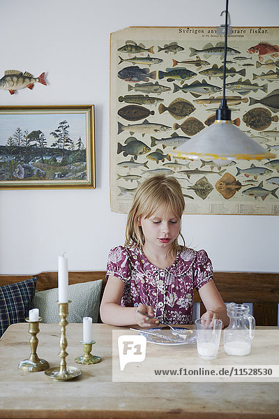 Girl eating by table