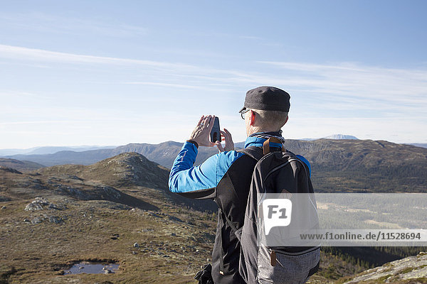 Hiker in mountains taking picture