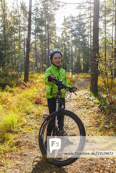 Boy with mountain bike in forest