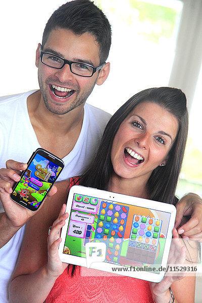 Frankreich  junges Paar spielt Candy Crush auf ihrem Handy und Tablett.