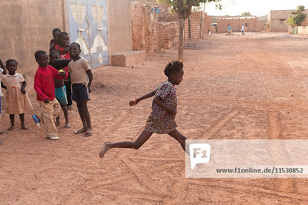 Burkina Faso  Ougadougou  Mädchen beim Hopscotch auf einer irdenen Gasse