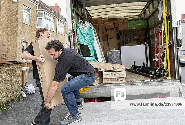 Umzugsunternehmen. Zwei Männer heben ein unhandliches Paket auf einen Lieferwagen.