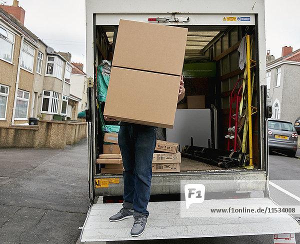 Umzugsunternehmen. Ein Mann auf der Heckklappe eines Lieferwagens mit einer großen Kiste. Umzugsunternehmen. Ein Mann auf der Heckklappe eines Lieferwagens mit einer großen Kiste.