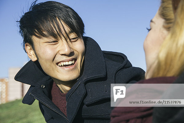 Portrait of laughing young man face to face with his girlfriend
