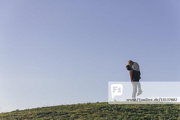 Junges Paar  das sich auf einem Hügel vor blauem Himmel küsst.