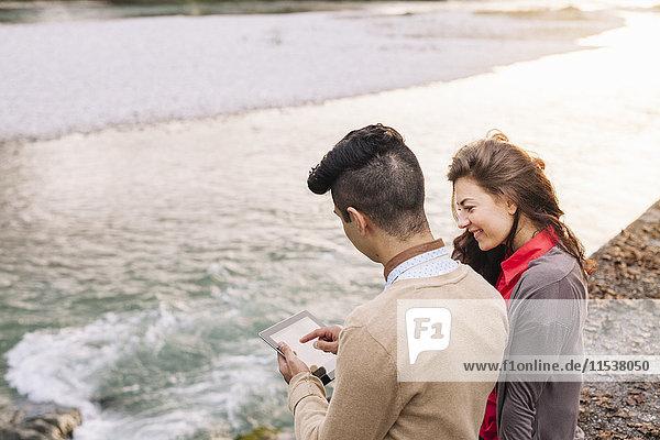 Italien  Belluno  junges Paar vor einem Fluss sitzend mit digitalem Tablett