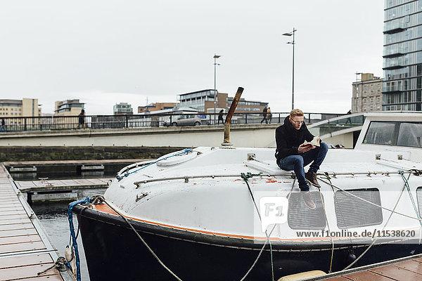Irland  Dublin  junger Mann sitzt auf einem Motorboot und liest ein Buch.