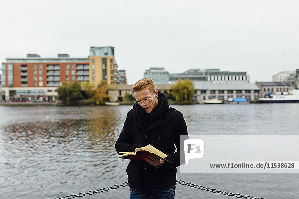 Irland  Dublin  junger Mann beim Lesen eines Buches vor dem Wasser