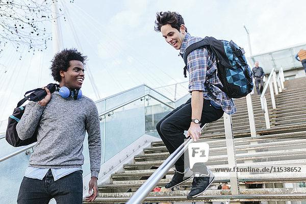 Junger Mann gleitet auf einem Treppengeländer