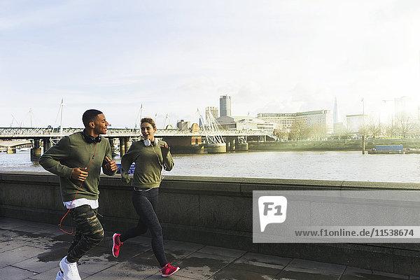 UK  London  Mann und Frau laufen auf dem Riverwalk