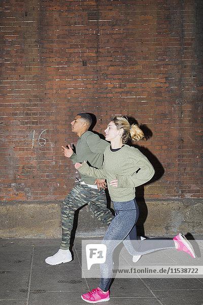 UK  London  Mann und Frau laufen nachts an der Ziegelmauer entlang.
