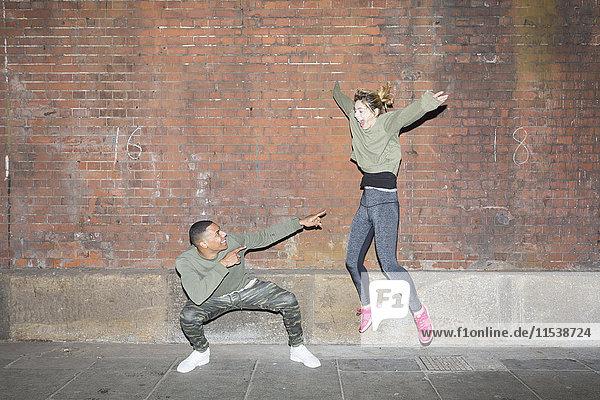 Verspieltes junges Paar vor der Backsteinmauer bei Nacht