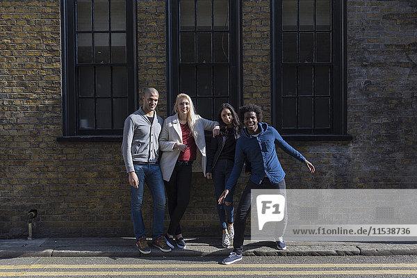 Gruppe glücklicher Freunde posiert vor dem Backsteingebäude