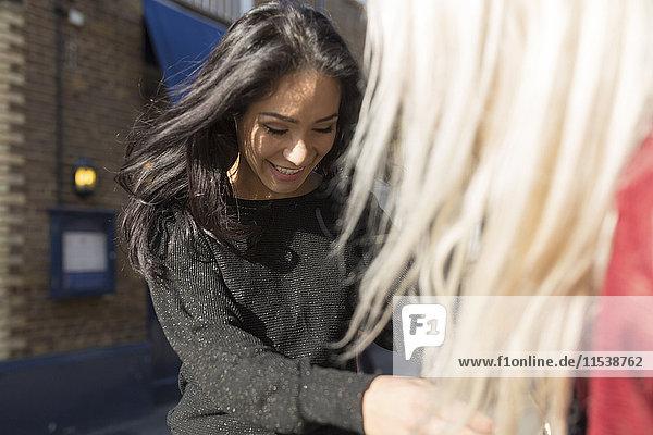 Lächelnde junge Frau hinterfragt Freundin