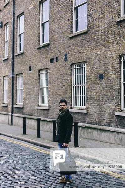 Junger lässiger Geschäftsmann auf der Straße stehend  Tasche tragend