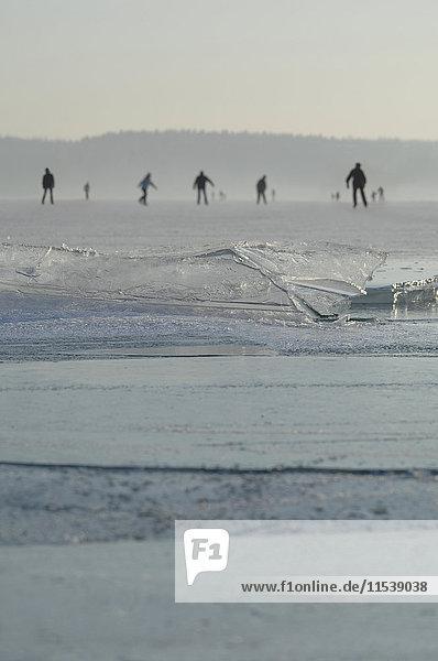 Deutschland  Menschen eislaufen auf gefrorenem See mit dünnem Eisschild