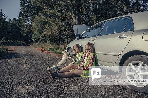 Zwei junge Frauen mit Sicherheitswesten sitzen auf der Straße und warten auf Hilfe für ihr beschädigtes Fahrzeug.