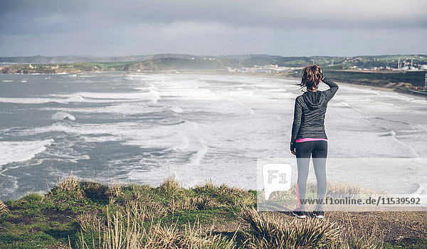 Sportliche mittlere erwachsene Frau auf Klippe mit Blick aufs Meer