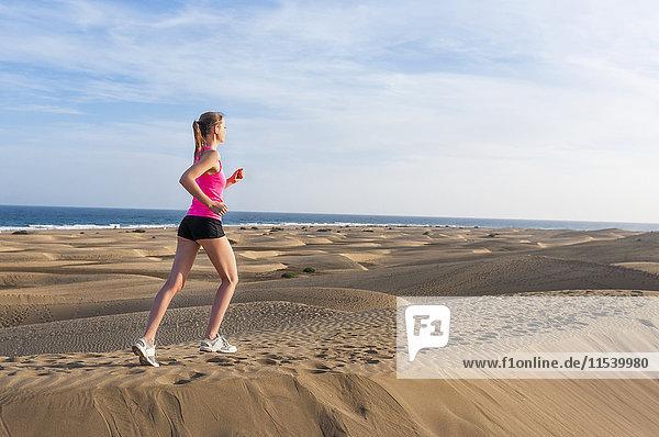Junge Frau beim Joggen am Strand