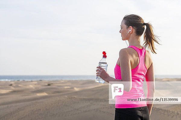 Junge Frau joggt am Strand  macht eine Pause