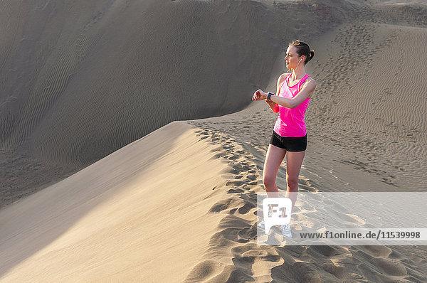 Junge Frau beim Joggen am Strand  Zeitkontrolle