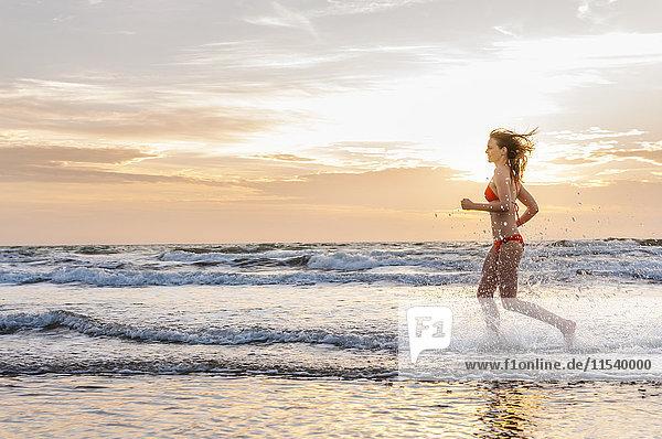 Frau im Bikini beim Joggen am Meer