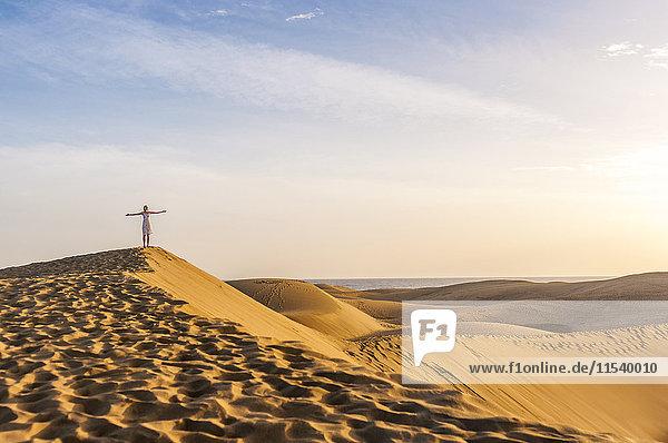 Frau auf Sanddüne stehend mit ausgestreckten Armen