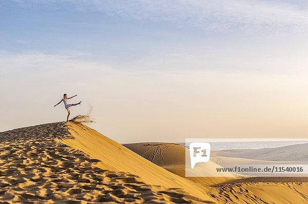 Frau auf Düne tritt Sand