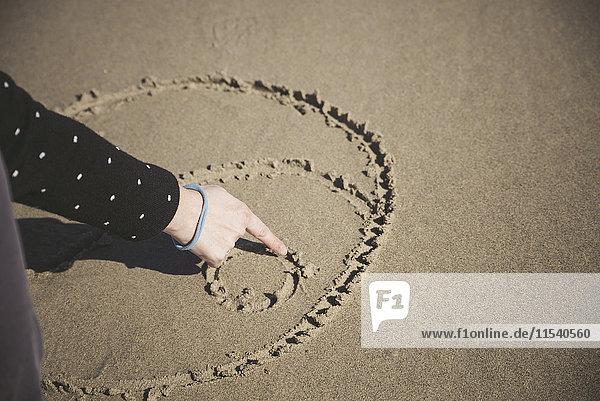 Frau kratzt Yin Yang Symbol im Sand eines Strandes  Nahaufnahme
