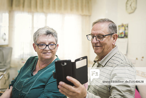 Senior couple looking at smartphone at home