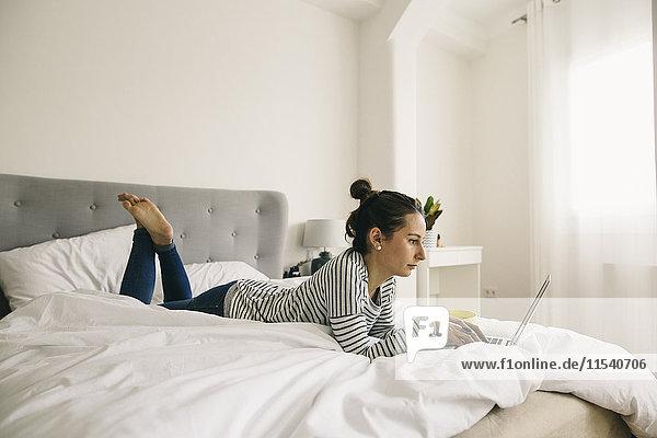 Entspannte Frau im Bett liegend mit Laptop