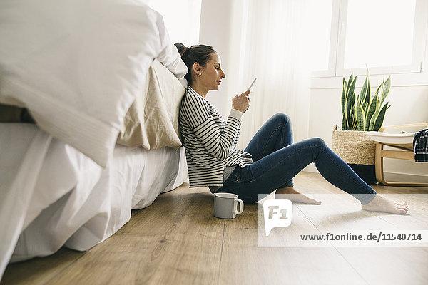 Entspannte Frau im Schlafzimmer mit Blick auf das Handy