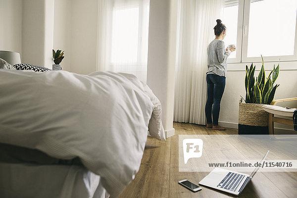 Frau schaut aus dem Schlafzimmerfenster