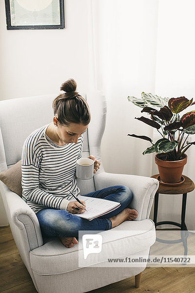 Woman sitting in armchair writing on notepad