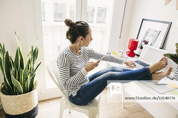 Frau zu Hause  die mit dem Laptop Füße auf den Tisch legt.