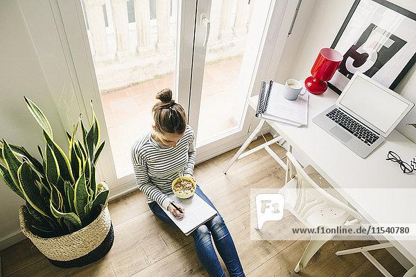 Frau sitzt auf dem Boden und schreibt auf Notizblock
