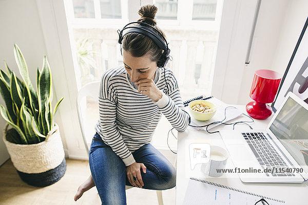 Frau zu Hause am Tisch sitzend mit Kopfhörer