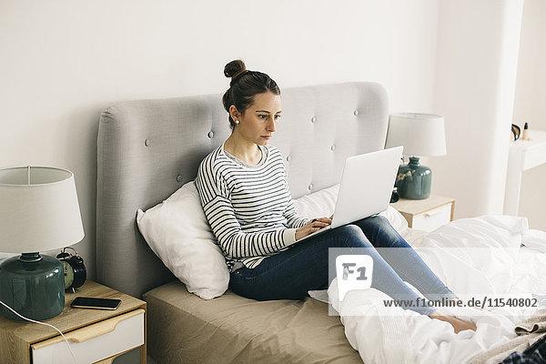 Frau im Bett sitzend mit Laptop