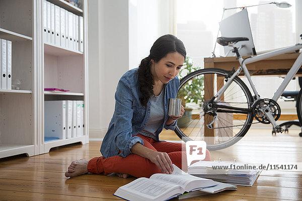 Frau sitzt auf dem Boden und liest Dokumente.