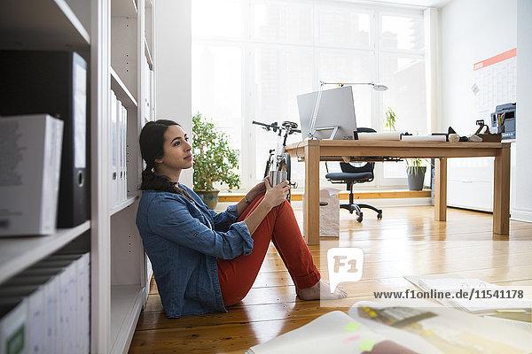 Frau sitzt im Büro auf dem Boden und macht eine Pause.