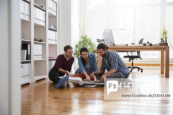 Drei kreative Geschäftsleute sitzen auf dem Boden und schauen in einer Mappe.