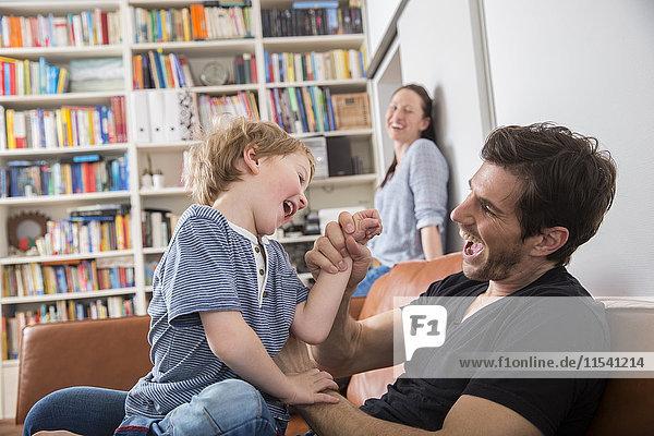 Vater und Sohn spielen auf dem Sofa  Mutter beobachtet im Hintergrund