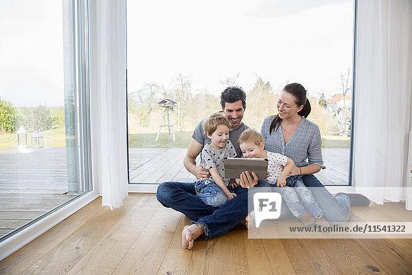 Glückliche Familie auf dem Boden sitzend  mit digitalem Tablett