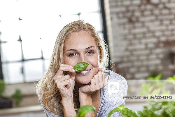 Porträt einer lächelnden blonden Frau mit Basilikumblatt