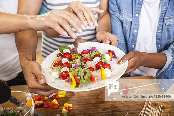 Hands reaching for healthy skewers on plate