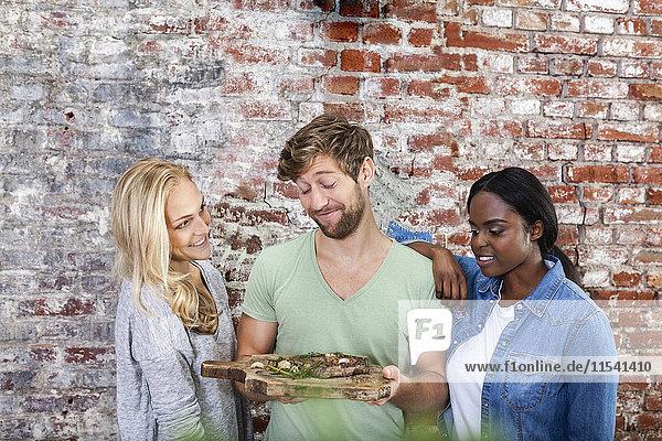 Porträt eines lächelnden Mannes mit zwei Frauen  die ein Brett mit Steak halten