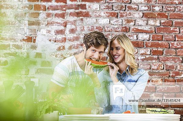 Ein glückliches junges Paar in der Küche,  das zusammen Wassermelone isst.