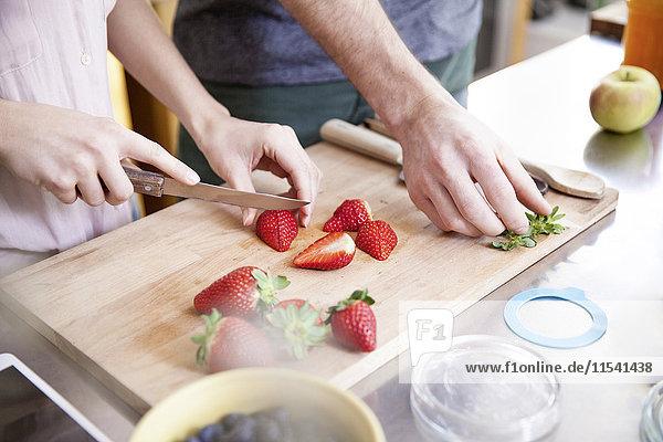 Paare schneiden Erdbeeren in der Küche